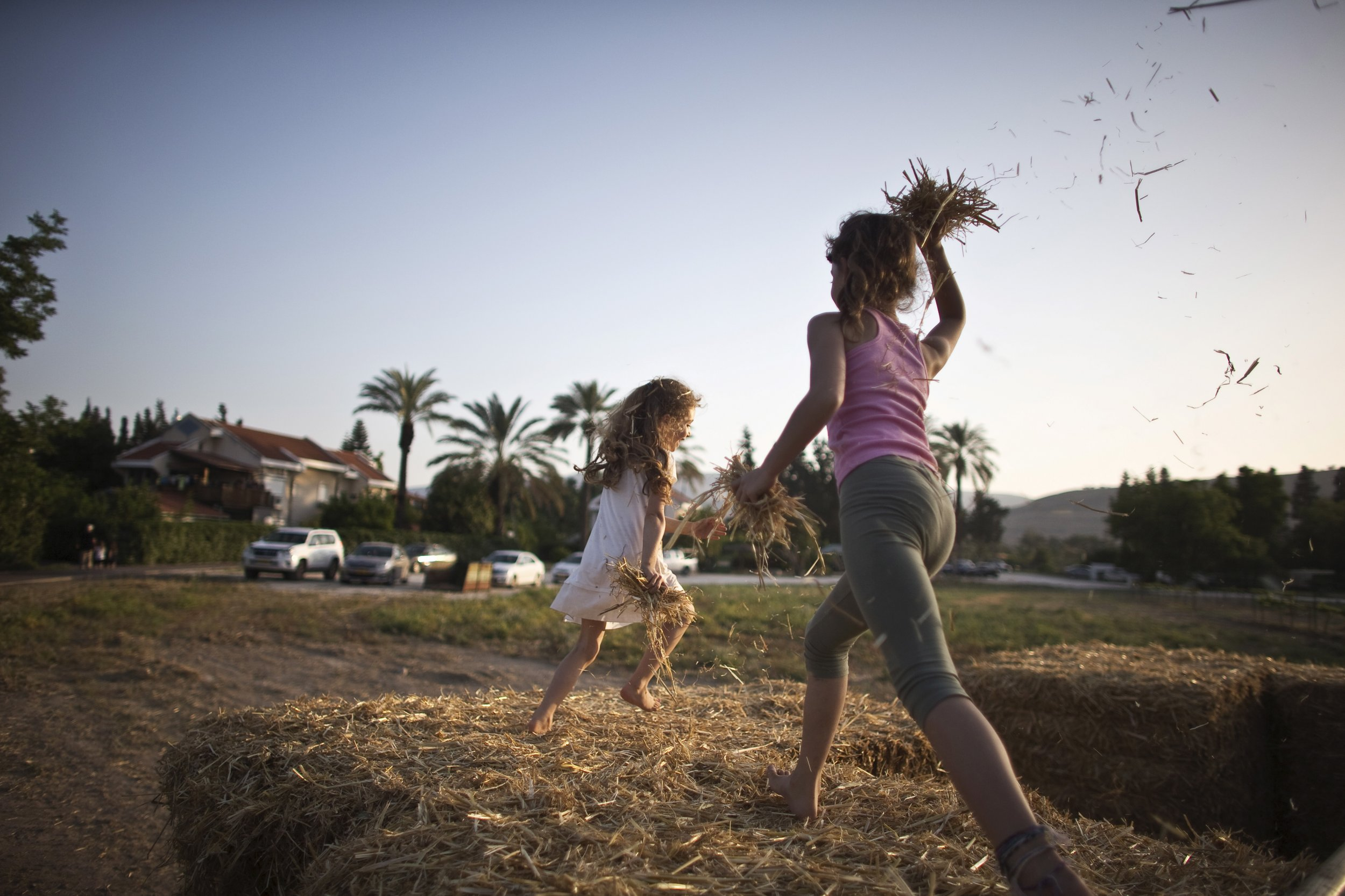 Girls playing in hay