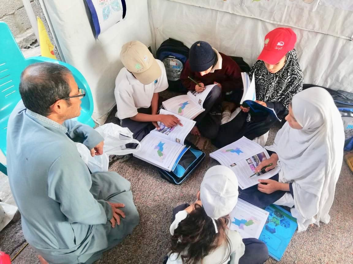 A Japanese expert with Pakistani children having non-formal education