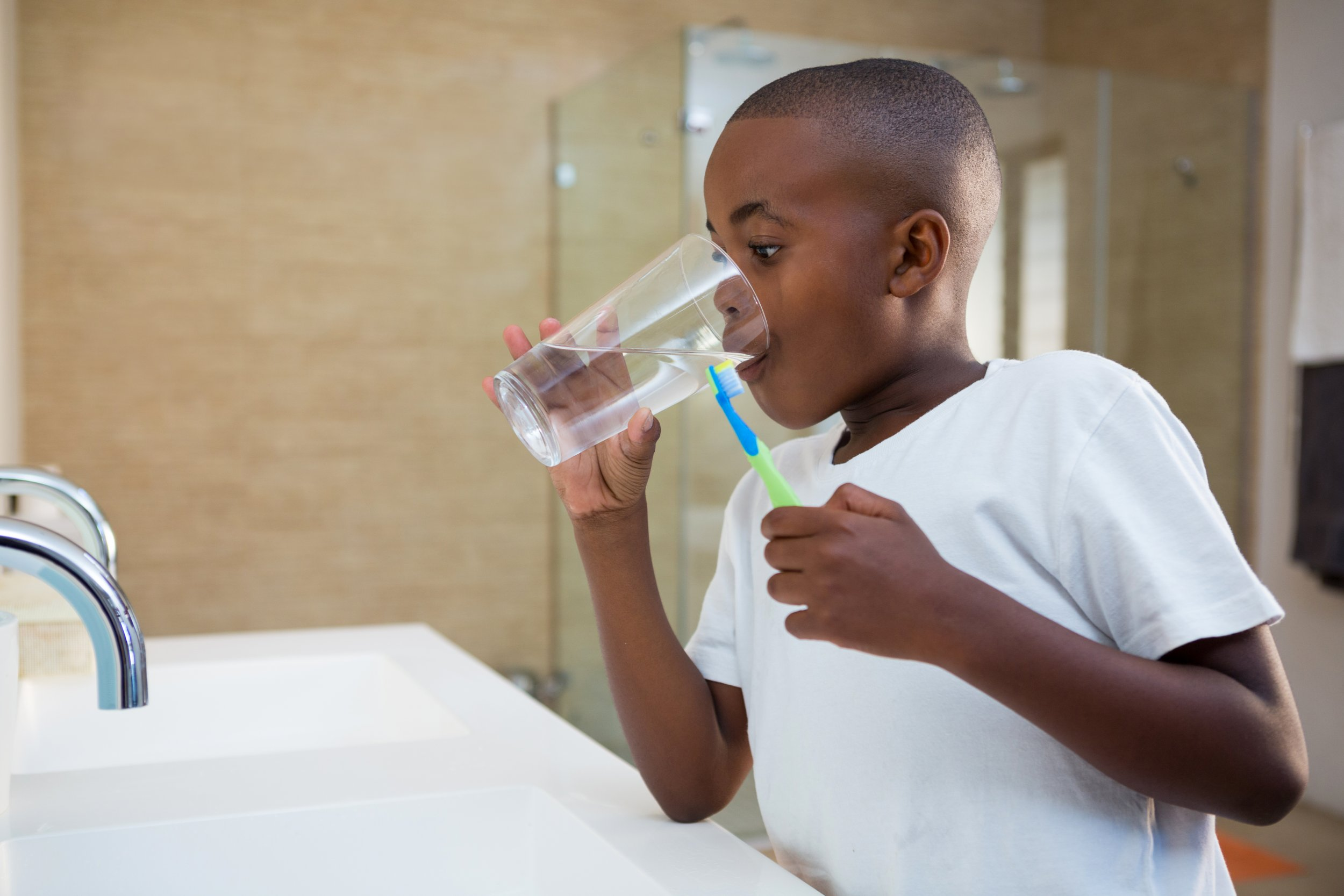 boy drinking water brushing teeth stock getty