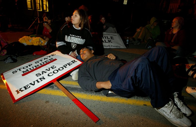 A couple rests outside of San Quentin State Prison in San Quentin, California, on February 9, 2004. They walked with other protestors from San Francisco in opposition to the execution of Kevin Cooper.