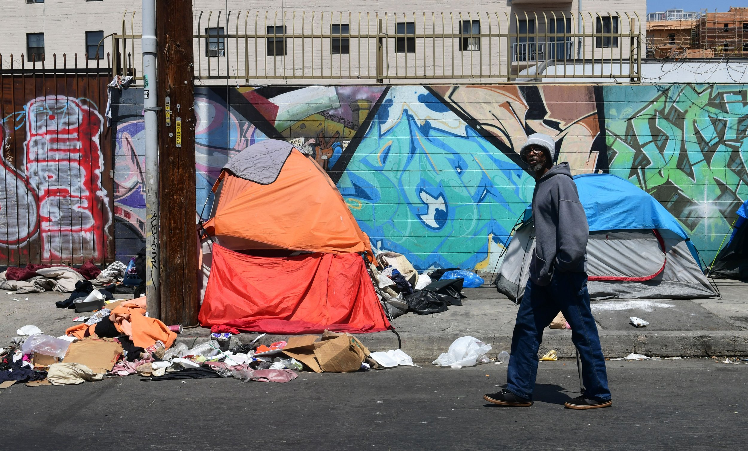 A pedestrian walks past tents and trash on a sidewalk in downtown Los Angeles on May 30, 2019.