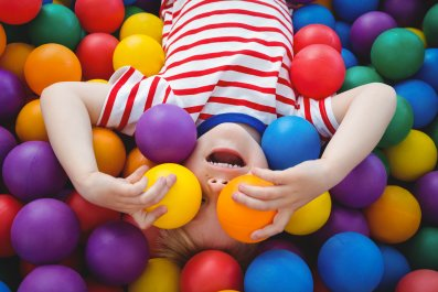 Cute smiling boy in sponge ball pool covering eyes with balls