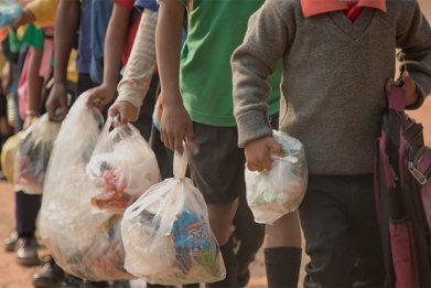 Children carry plastic waste to school