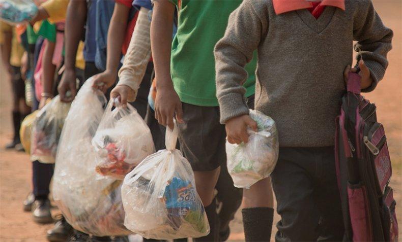 Children carry plastic waste to school