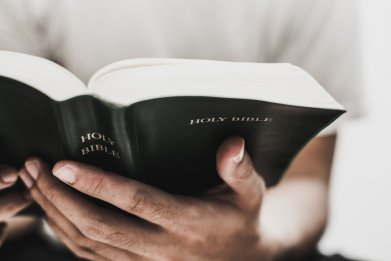 Hands holding an open bible