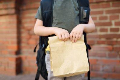 School child holding sack lunch