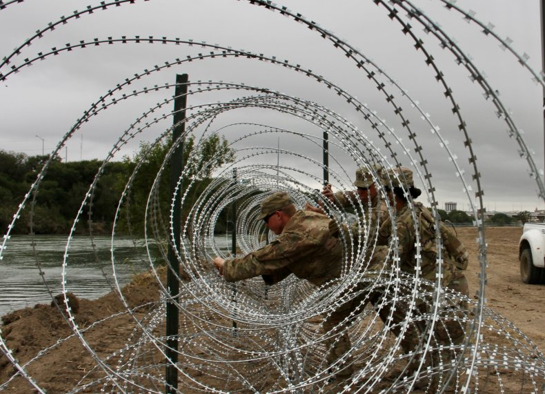 Soldier barbed wire border wall