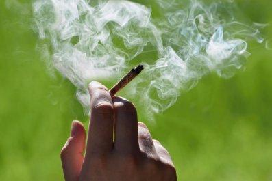 Hand holding a lit marijuana cigarette
