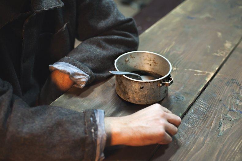 prisoner with food pot