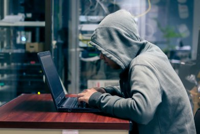 Young hacker using laptop