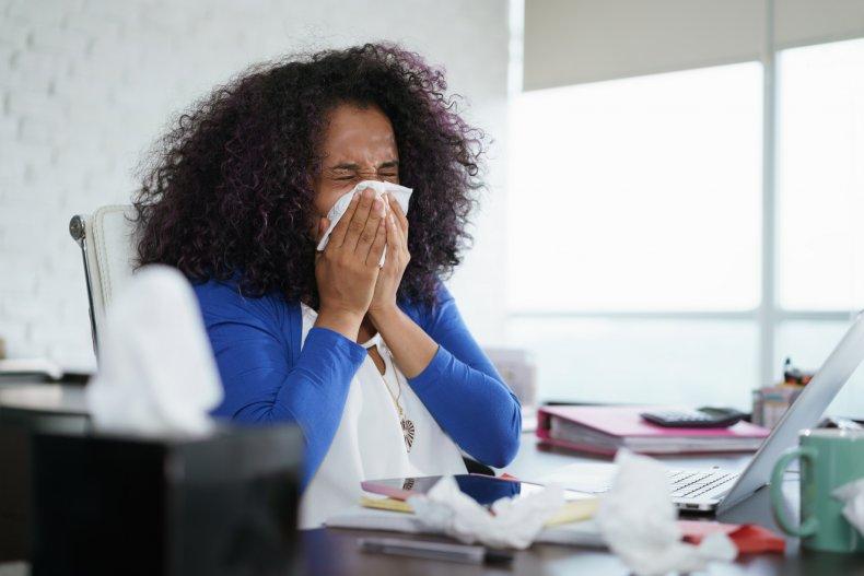 Woman sneezing at desk