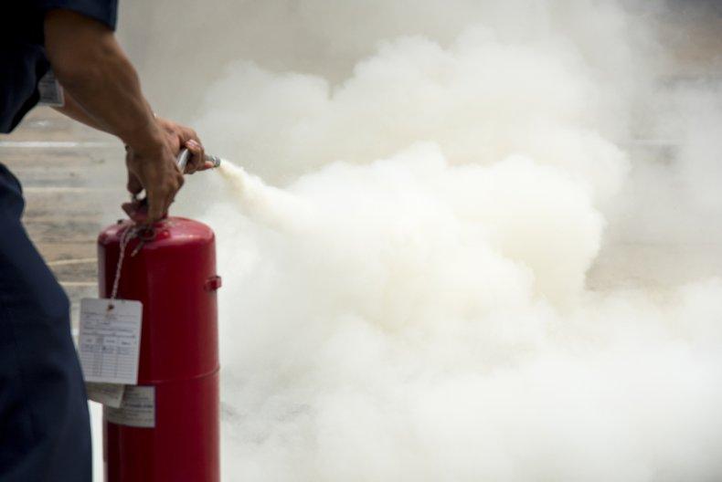 Man spraying a fire extinguisher