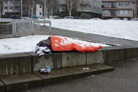 A homeless man sleeps in snow