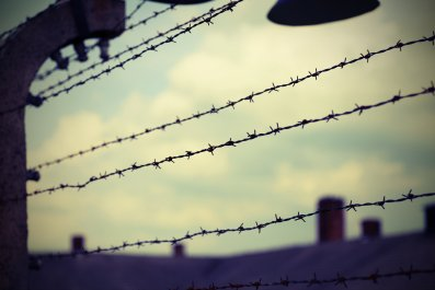 Barbed wire over wall of refugee camp