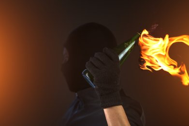 man holds molotov cocktail