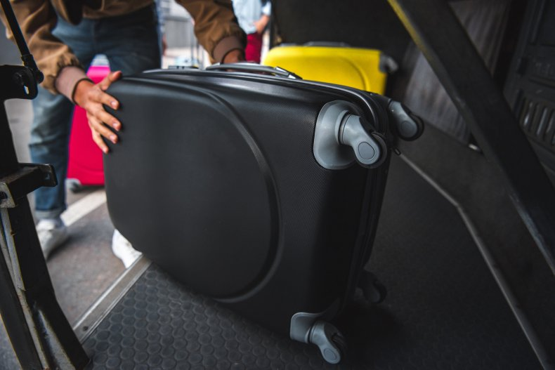 Luggage being loaded under a bus