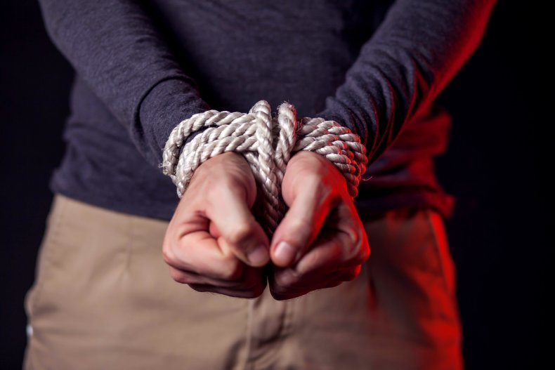 A man with wrists bound by rope