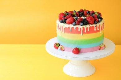 A rainbow cake on a cake stand