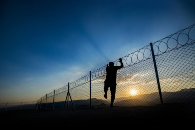 A man climbs a barbed wire fence
