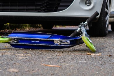Scooter on ground in front of parked car