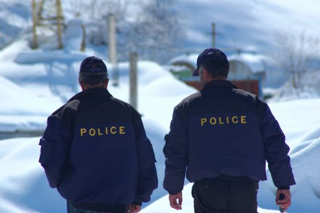 Two police officers walk in snow