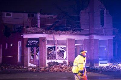 Emergency crews work near a damaged business