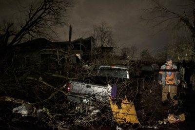 A man walks by a storm damaged pickup truck