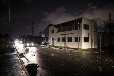 Vehicles pass by damaged buildings on Jefferson St.