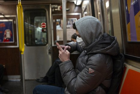 Man riding subway wearing a mask