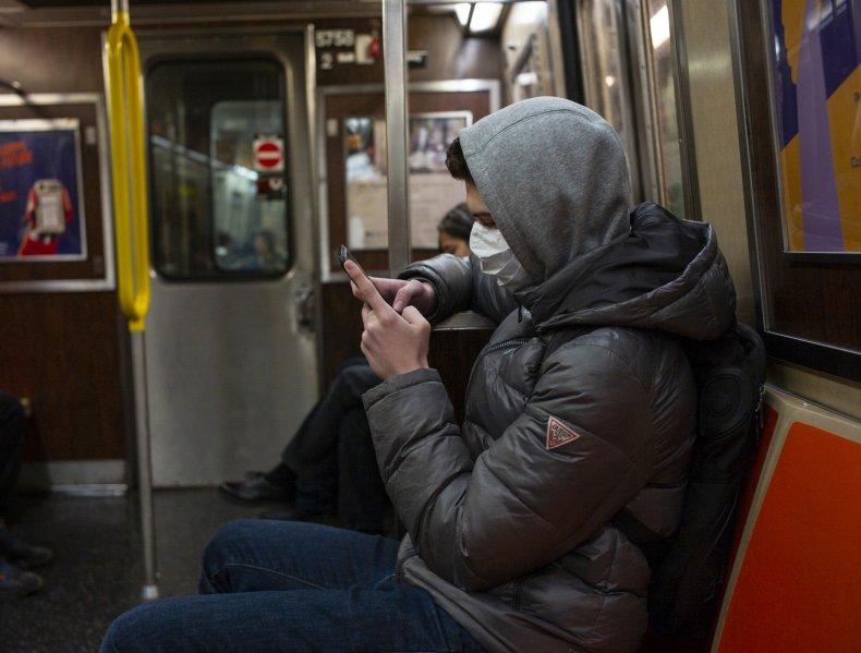 Man riding subway wearing a mask