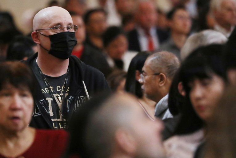 Worshipper at cathedral in LA wearing mask