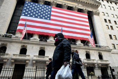 A man wearing a mask walks by the New York Stock Exchange (NYSE) on March 17, 2020 at Wall Street in New York City.