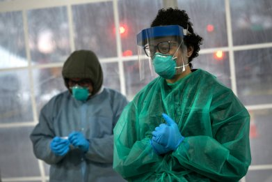 A doctor from SOMOS Community Care prepares to test a patient at a drive-thru testing center for coronavirus at Lehman College on March 28, 2020 in the Bronx, New York City.