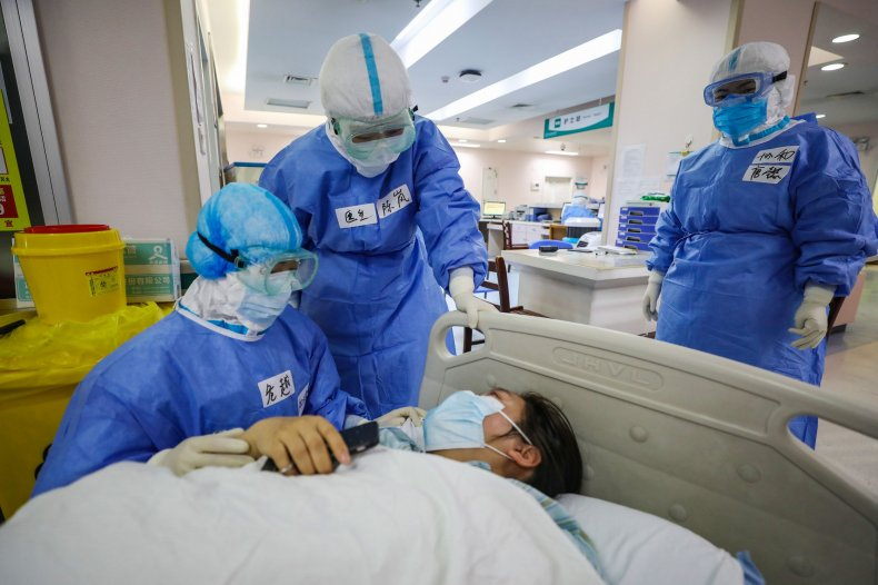 This photo taken on March 7, 2020 shows doctors comforting a pregnant woman, infected by the COVID-19 coronavirus, before her caesarean section at a gynaecology and obstetrics isolation ward in Xiehe hospital in Wuhan in China's central Hubei province.