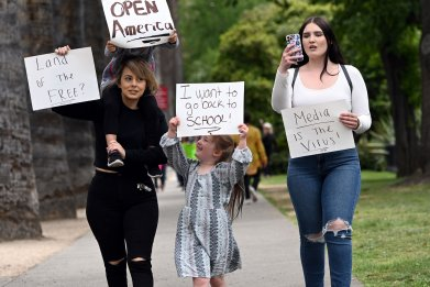 Family holds up signs protesting Coronavirus lockdown