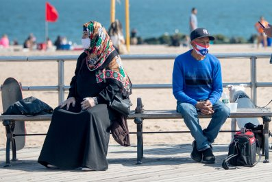 Two people sit on Coney Island boardwalk