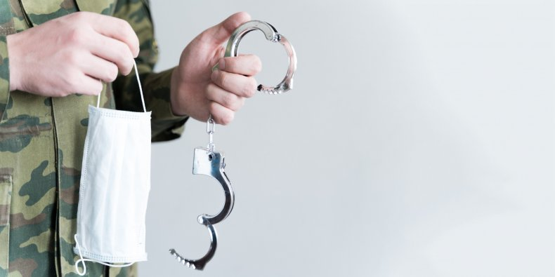 Officer holding face mask and handcuffs