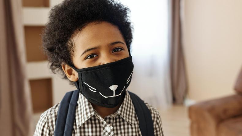 Boy wearing mask, smiling at camera