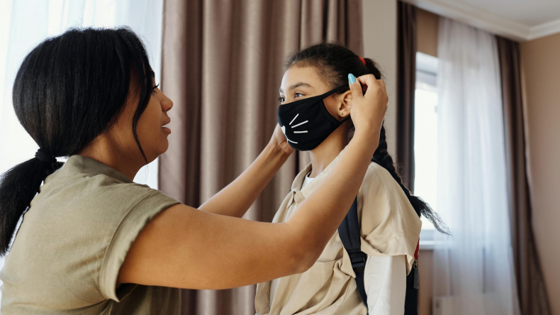Mom putting mask on daughter