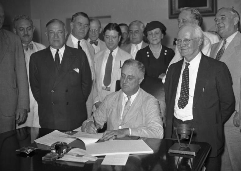 1935: Franklin D. Roosevelt signs Social Security Bill