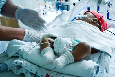 Sick baby treated by doctor in ICU
