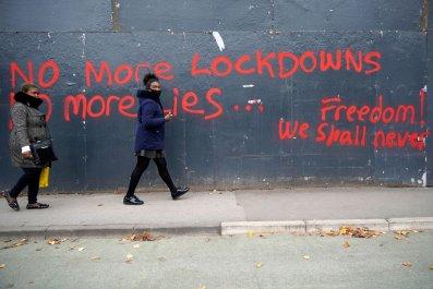 Women walk by anti-lockdown graffiti in Manchester