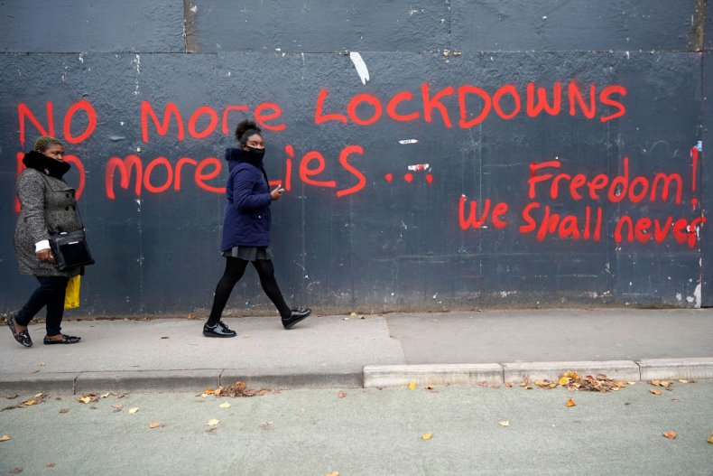 Women walk by anti-lockdown graffiti in Manchester