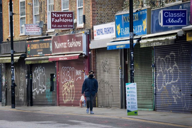A man walks past closed shops London