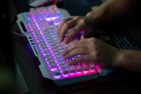 Person typing on backlit keyboard