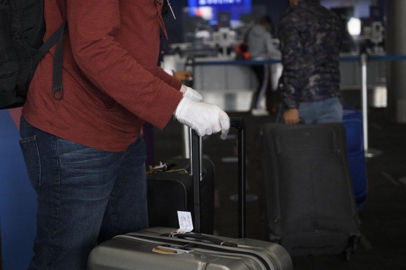 US-VIRUS-HEALTH-TRAVEL A passenger wearing gloves checks bags