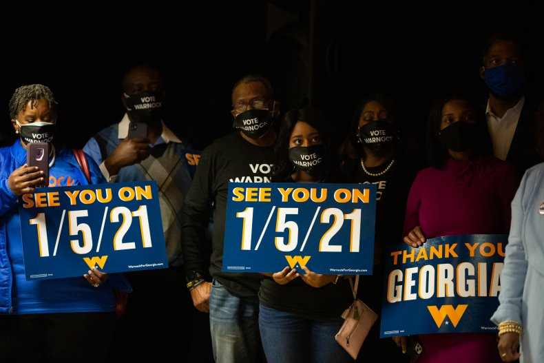 warnock supporters hold runoff signs in Georgia