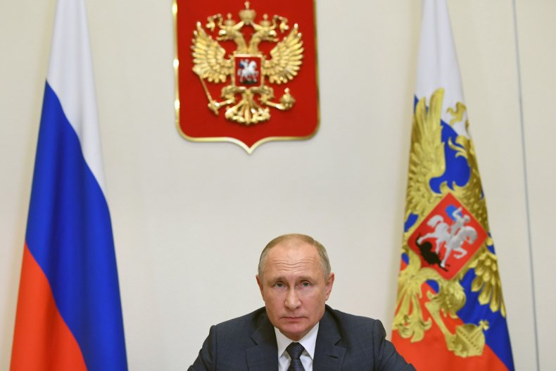Russia's Putin Sitting at Desk With Flags