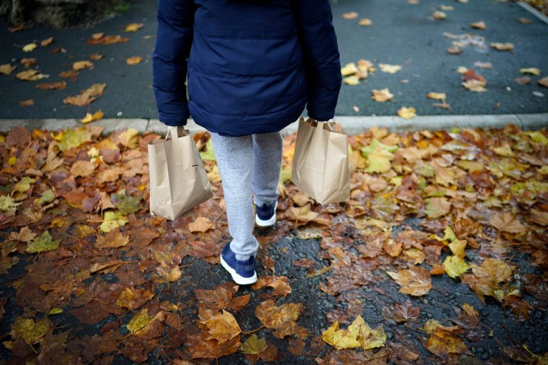 Young boy carries food parcels in England