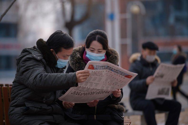 North Koreans read newspaper in Pyongyang